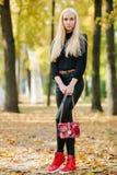 Muchacha adolescente hermosa rubia deportiva elegante joven en la presentación negra en el parque en un día de oro caliente de la Foto de archivo