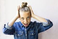 Muchacha adolescente hermosa sorprendida con la camisa de los vaqueros Imagen de archivo