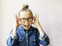 Muchacha adolescente hermosa sorprendida con los vidrios y la camisa de los vaqueros Fotos de archivo