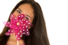 Muchacha adolescente hispánica linda que oculta detrás del molino de viento del juguete Fotos de archivo