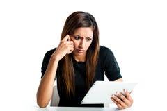 Muchacha adolescente india joven enojada con el ordenador de la tablilla Fotografía de archivo