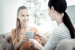 Muchacha adolescente inspirada que toma la taza del psicólogo de sexo femenino Fotos de archivo libres de regalías