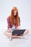 Muchacha adolescente integral que se sienta en el piso con el ordenador portátil Fotos de archivo libres de regalías