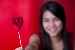 Muchacha adolescente joven biracial hermosa que sostiene el globo del corazón Imagenes de archivo