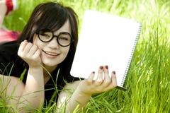 Muchacha adolescente joven con el cuaderno en la hierba verde Fotografía de archivo