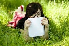 Muchacha adolescente joven con el cuaderno en la hierba verde Foto de archivo libre de regalías