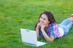 Muchacha adolescente joven con el ordenador portátil blanco Imagenes de archivo
