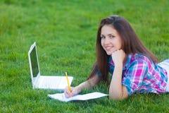 Muchacha adolescente joven con el ordenador portátil blanco Fotografía de archivo libre de regalías