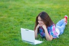 Muchacha adolescente joven con el ordenador portátil blanco Foto de archivo
