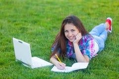 Muchacha adolescente joven con el ordenador portátil blanco Imagen de archivo libre de regalías