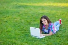 Muchacha adolescente joven con el ordenador portátil blanco Foto de archivo libre de regalías