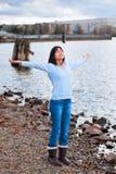 Muchacha adolescente joven con los brazos levantados y extendidos, elogiando a dios en orilla rocosa por el lago Foto de archivo