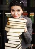 Muchacha adolescente joven en biblioteca entre cierre emocional de los libros encima del bookwarm Imagen de archivo