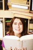 Muchacha adolescente joven en biblioteca entre los libros emocionales Fotos de archivo libres de regalías