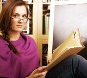 Muchacha adolescente joven en biblioteca entre los libros emocionales Imagen de archivo