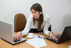 Muchacha adolescente joven en el escritorio de oficina con las computadoras portátiles Imágenes de archivo libres de regalías
