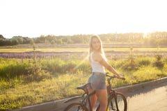 Muchacha adolescente joven en la bicicleta en sol Fotografía de archivo libre de regalías