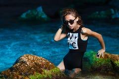 Muchacha adolescente joven en lanzamiento de la moda del mar en la puesta del sol Fotografía de archivo