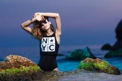 Muchacha adolescente joven en lanzamiento de la moda del mar en la puesta del sol Foto de archivo