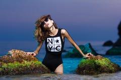 Muchacha adolescente joven en lanzamiento de la moda del mar en la puesta del sol Fotos de archivo libres de regalías