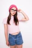 Muchacha adolescente joven en sombrero y vidrios rosados Imagenes de archivo