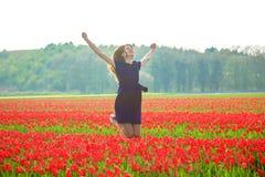 Muchacha adolescente joven feliz que salta para arriba contra un campo del tulipán de la primavera Foto de archivo