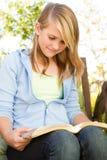 Muchacha adolescente joven fuera de la lectura Imágenes de archivo libres de regalías