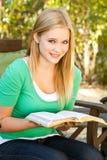 Muchacha adolescente joven fuera de la lectura Fotografía de archivo