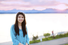 Muchacha adolescente joven hermosa que goza al aire libre por el lago en la puesta del sol Fotos de archivo