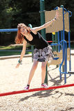 Muchacha adolescente joven que balancea en barra roja Imagen de archivo libre de regalías