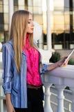 Muchacha adolescente joven que comprueba su tableta Imagenes de archivo