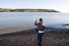 Muchacha adolescente joven que lanza una piedra Imagen de archivo