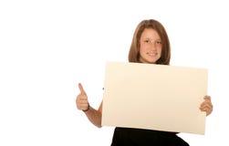 Muchacha adolescente joven que lleva a cabo a la tarjeta en blanco Imagen de archivo