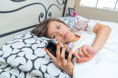 Muchacha adolescente joven que miente en cama con su teléfono celular Imágenes de archivo libres de regalías