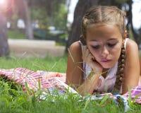 Muchacha adolescente joven que miente en hierba verde y el libro de lectura Fotografía de archivo