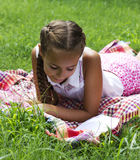 Muchacha adolescente joven que miente en hierba verde y el libro de lectura Fotos de archivo libres de regalías
