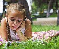 Muchacha adolescente joven que miente en hierba verde y el libro de lectura Imagen de archivo libre de regalías