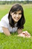 Muchacha adolescente joven que miente en la hierba verde, relajándose Imagen de archivo libre de regalías