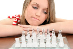 Muchacha adolescente joven que mira el conjunto de ajedrez Fotos de archivo libres de regalías