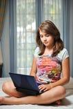 Muchacha adolescente joven que pone en su cama con el cuaderno Fotografía de archivo