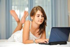 Muchacha adolescente joven que pone en su cama en la alineada blanca Imagen de archivo libre de regalías