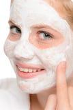 Muchacha adolescente joven que pone la crema facial de la máscara Fotografía de archivo