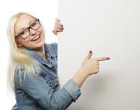 Muchacha adolescente joven que señala en tablero en blanco Fondo blanco Fotos de archivo libres de regalías