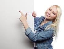 Muchacha adolescente joven que señala en tablero en blanco Fondo blanco Imagen de archivo libre de regalías