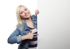 Muchacha adolescente joven que señala en tablero en blanco Fondo blanco Fotografía de archivo