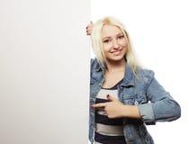 Muchacha adolescente joven que señala en tablero en blanco Fondo blanco Fotografía de archivo libre de regalías