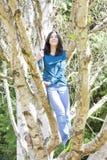 Muchacha adolescente joven que se coloca en ramas en el árbol de abedul, sonriendo Imágenes de archivo libres de regalías