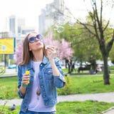 Muchacha adolescente joven que se divierte en el parque de la ciudad al aire libre Foto de archivo