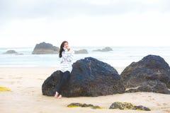 Muchacha adolescente joven que se inclina en roca grande por el océano, pensando Fotos de archivo libres de regalías