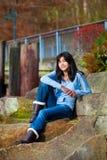 Muchacha adolescente joven que se relaja en el canto rodado grande a lo largo de la orilla del lago, sonriendo Fotos de archivo libres de regalías